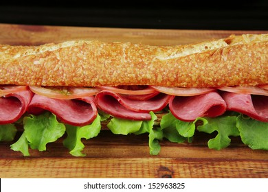 sandwich with smoked sausage on wooden plate over black background