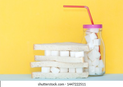 Sandwich with sugar  and glass full of sugar cubes. Too much sugar and unhealthy food concept.