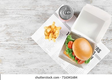 Sandwich with tasty fried fish in paper box and chips on table