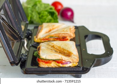 Sandwich toaster with toast and ingredients