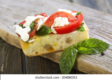 Sandwich with tomatoes, basil and mozzarella on wooden board.