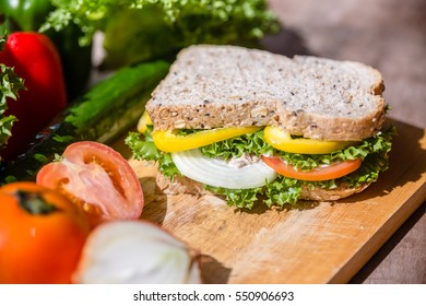 Sandwich with tuna and vegetables on rye bread on wood background