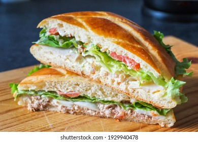 Sandwich with tuna and vegetables on wooden board.