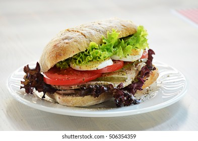 Sandwich with vegetables and egg on white plate on white table.