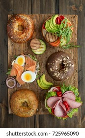a sandwich with vegetables, salmon and ham. top view. on a wooden table
