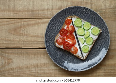 Sandwich with white cream cheese, red cherry tomato and cucumber served in a grey plate on wooden background. Breakfast toasts