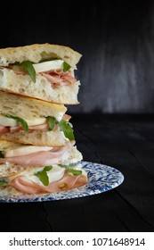 Sandwich with white pizza, mortadella, mozzarella cheese and arugula on black background.