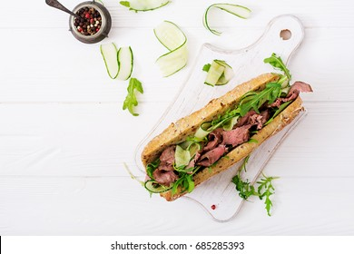 Sandwich of whole wheat bread with roast beef, cucumber and arugula. Top view. Flat lay.