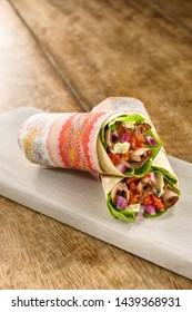 Sandwich wrap with roast beef, lettuce, gorgonzola cheese and tomato, on a wooden table
