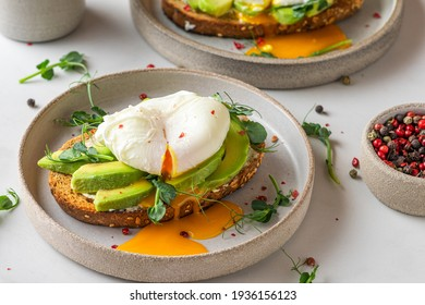Sandwiches with avocado, poached egg, sprouts and cheese for healthy breakfast on white background. top view. Healthy diet food