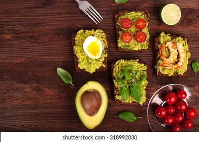 Sandwiches with avocado puree with guacamole with various toppings such as egg, shrimp, tomatoes and basil leaves on a brown wooden background. Place for writing text