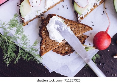 Sandwiches with avocado, radish, arugula, cheese and nuts on a rye bread with sunflower seeds for healthy breakfast on dark wooden background. Vegetarian food. Top view.