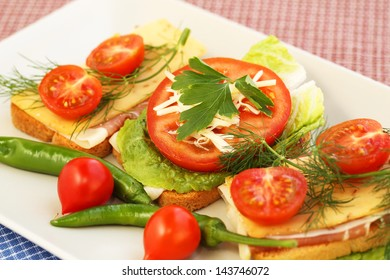 Sandwiches with bacon, cheese, cherry tomato and dill on plate.