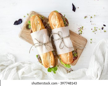 Sandwiches with beef, fresh vegetables and herbs on rustic wooden chopping board over white wood backdrop, top view, horizontal