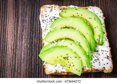Sandwiches from bread with slices, zvezdami, hearts from avocado and curd cheese on a brown wooden background.
