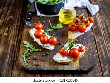 sandwiches with cheese and cherry tomatoes on a dark jar board on a wooden table close-up