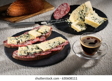 Sandwiches with cheese of Dorblu and raw smoked sausage on black slate plates, a cheese knife and a cup of hot coffee