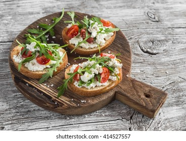 Sandwiches with cheese, tomatoes and arugula on a rustic wooden board. Healthy food