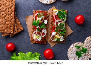 Сrisp sandwiches with cheese, tomatoes, lettuce, onion, fresh parsley and dill. Snack Bread and fiber food. Rye and wheat crisp bread and rice bread. Flat lay, top view