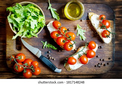 sandwiches with cherry tomatoes salad oil seasoning on a wooden board on a dark wooden table top view