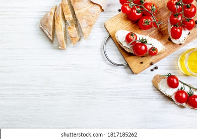 sandwiches with cherry tomatoes salad oil seasoning on a wooden board on a white wooden table top view
