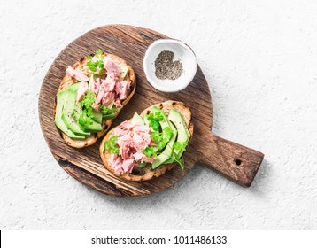 Sandwiches with cream cheese, avocado and tuna fish on wooden cutting board on white background, top view. Healthy breakfast or snack