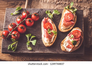 Sandwiches with cream cheese and ham on the wooden board
