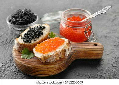 Sandwiches with delicious caviar on dark background