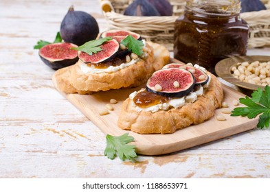 Sandwiches with figs, jam and cream cheese on a wooden background. Selective focus.