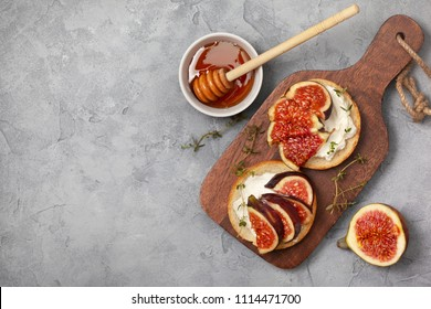 sandwiches with figs, ricotta, honey and thyme on a gray background. view from above