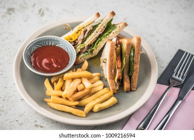 Sandwiches, French fries and ketchup on a light table. Fresh hot food.