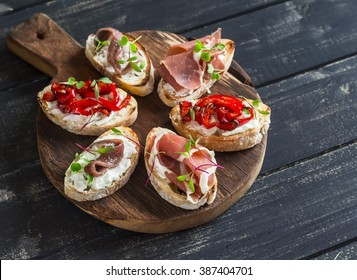Sandwiches with goat cheese, anchovies, roasted peppers, ham on a wooden rustic board. Delicious snack or appetizer with wine