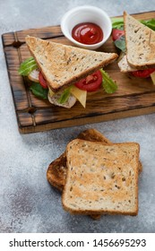 Sandwiches with grain bread, chicken fillet, cheese and vegetables, vertical shot, elevated view