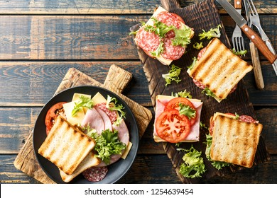 sandwiches with grilled toast ham salami cheese tomatoes and lettuce
