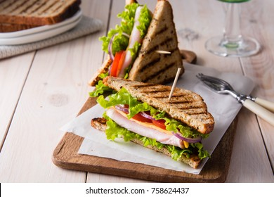 Sandwiches with ham, cheese, tomatoes and  salad with toasted bread.