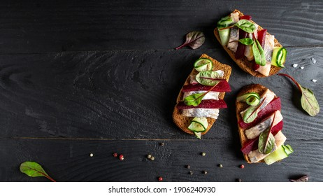 Sandwiches with herring, onions and beetroot salad, fresh cucumber. Tradition Danish open sandwich smorrebrod with herrin. Long banner format, top view.
