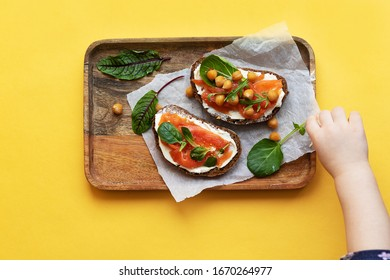 Sandwiches lie on a wooden tray. Stuffing of red fish and greens. The child reaches for a hand. Bright yellow background. Breakfast or healthy snack option.