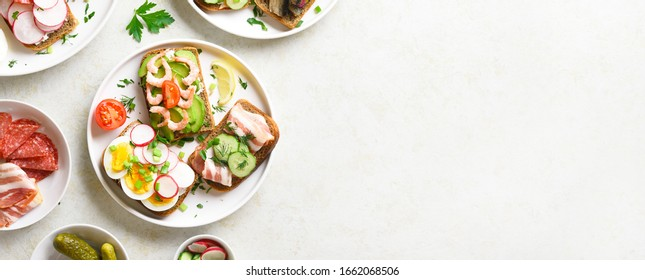 Sandwiches with meat, vegetables, seafood. Assortment open sandwiches on light stone background with free text space. Tasty healthy snack. Top view, flat lay.