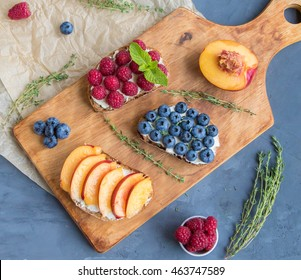 Sandwiches with mild cream cheese and different berries on wooden cutting board, top view