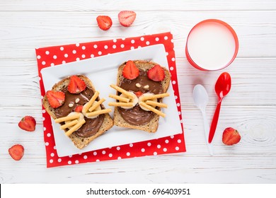 Sandwiches and milk for children's breakfast. Funny cats face sandwiches with berry, chocolate, banana, nuts. Top view
