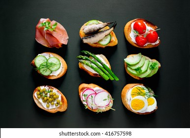 Sandwiches on a dark background, or assorted canapes, top view