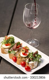 Sandwiches on a plate and wine splash in glass