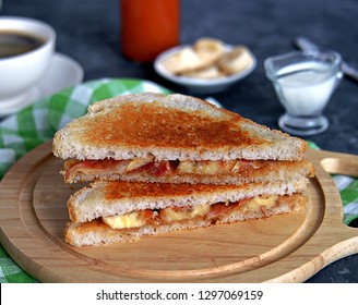 Sandwiches with peanut butter, banana and fried bacon on a wooden board.