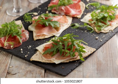Sandwiches with Prosciutto, sliced cheese, and rocket salad on wedges of piadina