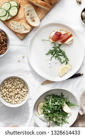 Sandwiches with prosciutto, vegetables and arugula salad on light background, top view. Healthy breakfast, snack