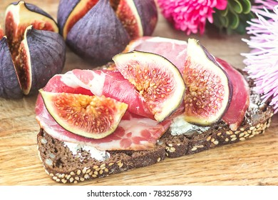 Sandwiches with ricotta cheese, fresh figs and ham, bacon ham prosciutto on rustic wooden cutting board,  top view. Delicious tasty appetizer, ideal as an aperitif. Selective focus, close up, top view