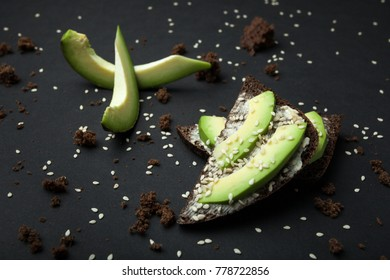 Sandwiches with rye bread, fresh sliced avocado and scattered crumbs on a black background.