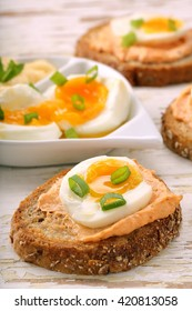 Sandwiches with salmon paste and egg on white wooden background