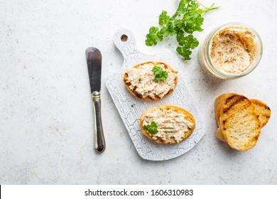 Sandwiches with salmon pate and baguette, fish bruschetta, top view. Rustic homemade Italian cuisine.