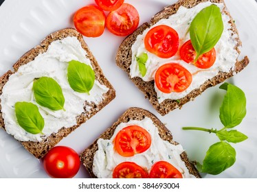 Sandwiches with soft cream cheese, cherry tomatoes and fresh basil on white plate